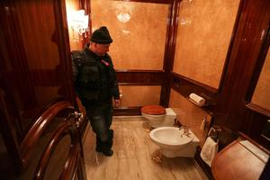 A man stands inside a lavatory as anti-government protesters and journalists walk on the grounds of the Mezhyhirya residence of Ukraine's President Viktor Yanukovich