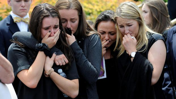 Mourners cry as the caskets of cousins Olivia Burke, 21, and Ashley Donohoe, 22, are placed in hearses following services at St. Joseph Catholic Church in Cotati, California on Saturday (AP Photo/Michael Short)