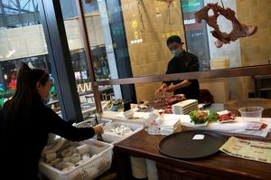 A chef wearing a face mask prepares beef as a waitress sorts tableware at a beef hotpot restaurant in Beijing, amid an outbreak of the novel coronavirus disease (COVID-19) in the country, China April 7, 2020. Picture taken April 7, 2020. REUTERS/Tingshu Wang