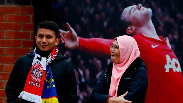 Two Manchester United fans in front of a picture of out-of-favour Wayne Rooney outside Old Trafford last night. Photo: Jason Cairnduff/Action Images via Reuters