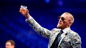 UFC lightweight champion Conor McGregor raises a glass of 'Notorious Irish Whiskey' during post-fight news conference