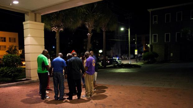 A small prayer circle forms nearby where police are responding to a shooting at the Emanuel AME Church in Charleston, South Carolina June 17, 2015. A gunman opened fire on Wednesday evening at the historic African-American church in downtown Charleston, a U.S. police official said.  REUTERS/Randall Hill