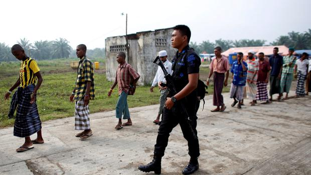 An Indonesian police officer walks beside Rohingya migrants who arrived in Indonesia last week by boat as they walk to collect breakfast at a temporary shelter in Aceh Timur regency near Langsa in Indonesia's Aceh Province May 27, 2015.  REUTERS/Darren Whiteside