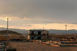 A lone house sits on the scarred landscape, inside the exclusion zone, close to the devastated Fukushima Daiichi Nuclear Power Plant on February. Photo by Christopher Furlong/Getty Images