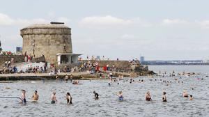 People enjoy the sunshine with high temperatures at Seapoint, Dublin. Photo: Leon Farrell/Rollingnews.