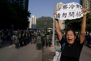 An anti-government protester holds a sign during a march in Tuen Mun, Hong Kong, China September 21, 2019. REUTERS/Aly Song