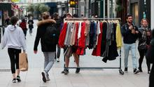 PREPARATION: A man wheels a rack of clothing down Grafton Street in Dublin yesterday as phase two of Ireland's coronavirus recovery road map is set to begin. Photo: Brian Lawless