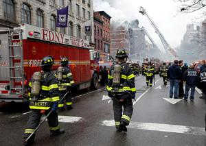 New York City Fire Department firefighters walk on 2nd Avenue towards the site of where a residential apartment was engulfed in flames in New York City. Reuters /Mike Segar