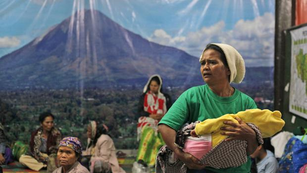 Villagers rest inside a temporary shelter with a large banner depicting Mount Sinabung, after they evacuated their homes on the slope of the volcano, in Karo, North Sumatra, Indonesia, Wednesday, June 3, 2015. (AP Photo/Binsar Bakkara)