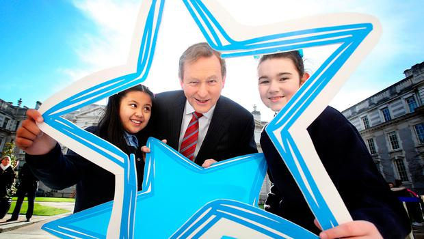 Taoiseach Enda Kenny with Sosfia Corpuz, left, and Emily Lee-Duff from St Vincent's Girls National School, Dublin, yesterday at the launch of the Blue Star Programme for this school year. Photo: Tom Burke