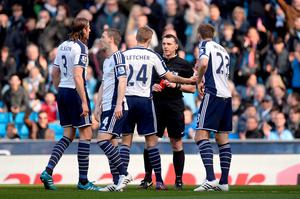 West Bromwich Albion's Gareth McAuley (right) is shown the red card by referee Neil Swarbrick during the Barclays Premier League match at the Etihad Stadium, Manchester.