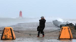 A  lady braves the wind at the South Bull as winds from Storm Frank  whip up the sea.Picture Credit :Frank Mc Grath