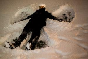 Airman Apprentice Franklen Garett makes a snow angel during Christmas Tree Lighting Ceremony at the Gerald R. Ford Presidential Museum in Grand Rapids, Mich. on Monday