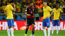 Germany's Sami Khedira walks past Brazil's Fred , Oscar and Fernandinho as they react to him scoring the fifth goal