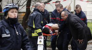 Firefighters carry a victim on a stretcher at the scene after a shooting at the Paris offices of Charlie Hebdo, a satirical newspaper. Photo: Reuters