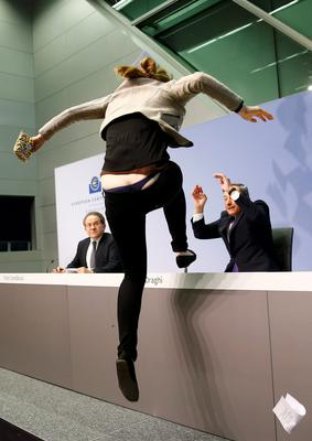 A protester jumps on the table in front of the European Central Bank President Mario Draghi during a news conference in Frankfurt