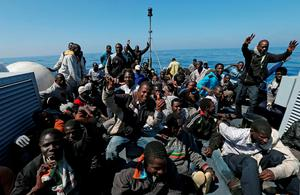 Migrants celebrate aboard the Italian Coast Guard vessel Denaro after being rescued off the Libyan coast in this picture released yesterday. Photo: AP