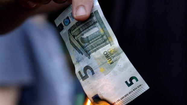 An anti-austerity protester burns a euro note during a protest outside the European Union offices in Athens