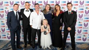 Ella Chadwick (front) wins Child of Courage award from (left to right) Dermot O'Leary, Robbie Williams Simon Cowell, Karen Chadwick (Ella's mum), Ayda Field and Louis Tomlinson during the Pride Of Britain Awards 2018 (Steve Parsons/PA)