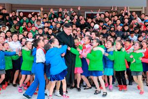 North Korean leader Kim Jong Un is hugged by children during his visit to Samjiyon County in this undated photo released by North Korea's Korean Central News Agency (KCNA) in Pyongyang November 28, 2016. REUTERS/KCNA