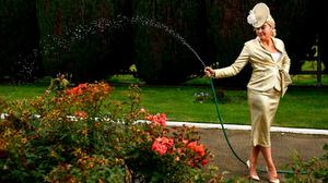 Louise Allen, from Slane, Co Meath, waters the grass in her outfit. Photo: Harry Murphy/Sportsfile