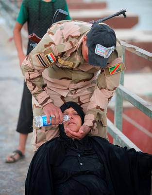 An Iraqi soldier gives water to a displaced woman at the outskirts of Baghdad, May 19, 2015. REUTERS/Stringer