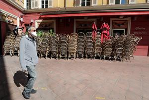 A man wearing a protective face mask walks past stacked chairs of a closed restaurant in Nice, as a lockdown is imposed to slow the rate of the coronavirus disease (COVID-19) in France. Photo: REUTERS/Eric Gaillard