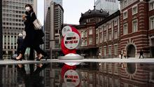 A countdown clock for the Tokyo 2020 Olympics is reflected in a puddle of water outside Tokyo Station in Tokyo on Monday, March 23. Photo: AP/Jae C Hong