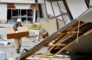A resident brings household goods out from collapsed houses after an earthquake in Hakuba town, Nagano prefecture, in this photo taken by Kyodo November 23, 2014.