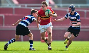 Colin Sisk, CBC, breaks through a tackle from Mark Edwards, left, and Jack Hennessy, Crescent College Comprehensive