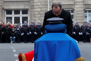 French President Francois Hollande leans over the coffin of late Police officer Franck Brinsolaro during a ceremony to pay tribute to the three police officers killed in the attacks, in Paris, France. Police officers Ahmed Merabet, 40, Franck Brinsolaro, 49, were killed during the attacks at Charlie Hebdo, and Clarissa Jean-Philippe killed in Montrouge last week (AP Photo/Francois Mori)