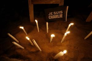 "A placard reading ""I am Charlie"" and candles are placed as a tribute to the victims following a shooting by gunmen at the offices of French weekly newspaper Charlie Hebdo in Paris, during a candlelight vigil in Abidjian. Reuters"