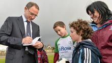 Ireland manager Martin O'Neill signs an autograph for Lee Park, aged 11, from Castleconnell, Limerick, during a visit to the Markets Field Project