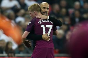 Manchester City's Spanish manager Pep Guardiola (R) embraces Manchester City's Belgian midfielder Kevin De Bruyne as he leaves the pitch substituted during the English Premier League football match between Tottenham Hotspur and Manchester City at Wembley Stadium in London, on April 14, 2018. / AFP PHOTO / Ian KINGTON /