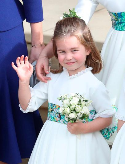 Princess Charlotte waves on the steps of St George's Chapel in Windsor Castle after the wedding of Princess Eugenie and Jack Brooksbank, in Windsor, Britain October 12, 2018.  Andrew Matthews/Pool via REUTERS