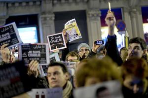 "People hold pencils and placards reading ""I Am Charlie"" (Je Suis Charlie) in front of the Consulate of France in Barcelona (Getty Images)"