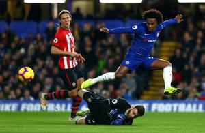Willian of Chelsea FC leaps over Angus Gunn of Southampton FC during the Premier League match against Southampton at Stamford Bridge (Photo by Chloe Knott - Danehouse/Getty Images)