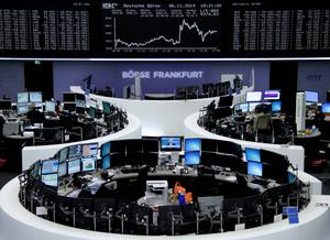 Traders are pictured at their desks in front of the DAX board at the Frankfurt stock exchange.     Reuters