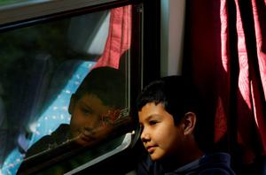 A boy looks out of a window as a train with hundreds of migrants leaves the Keleti Railway Station in Budapest, Hungary, Thursday, Sept. 3, 2015. Over 150,000 migrants have reached Hungary this year, most coming through the southern border with Serbia. Many apply for asylum but quickly try to leave for richer EU countries. (AP Photo/Petr David Josek)