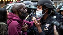 A protester and a police officer shake hands in the middle of a standoff during a solidarity rally calling for justice over the death of George Floyd Tuesday, June 2, 2020, in New York. (AP Photo/Wong Maye-E)