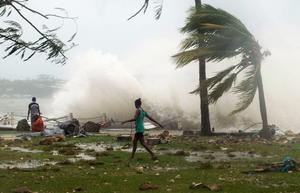 Local residents walk past debris as a wave breaks nearby in Port Vila, the capital city of the Pacific island nation of Vanuatu March 14, 2015. Winds of up to 250 kilometers an hour (155 mph) ripped metal roofs off houses and downed trees in Vanuatu on Saturday   REUTERS/UNICEF Pacific/Handout via Reuters