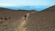 Walking on Pico Viejo in Teide National Park, Tenerife. La Gomera Island is in the distance. Photo: Deposit