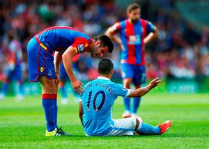 An injured Sergio Aguero of Manchester City in discussion with Scott Dann