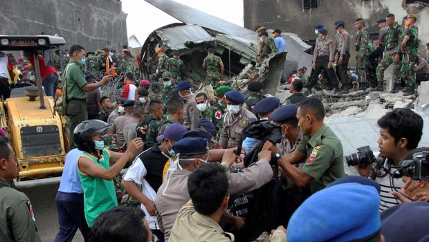 Security forces and rescue teams remove the bodies of victims from the wreckage of an Indonesian military C-130 Hercules transport plane after it crashed into a residential area in the North Sumatra city of Medan, Indonesia. Reuters/Irsan Mulyadi/Antara Foto