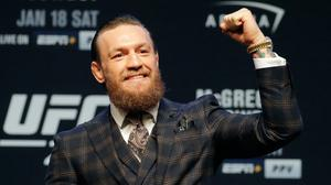 Conor McGregor motions to the crowd during a news conference for UFC 246