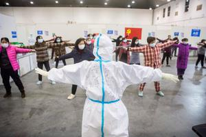 Crisis response: A health worker in Wuhan leads suspected coronavirus infectees in gentle exercise in a converted exhibition centre. Photo: STR/AFP via Getty Images