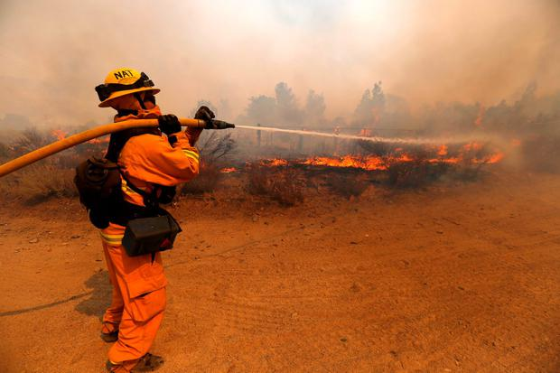 A firefighter sprays water while battling the Blue Cut fire in Phelan, California U.S., August 17, 2016. REUTERS/Mario Anzuoni