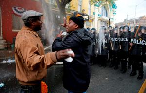 A Baltimore resident (R) trying to restore order in his neighborhood speaks to a protester during clashes in Baltimore. Photo: Reuters