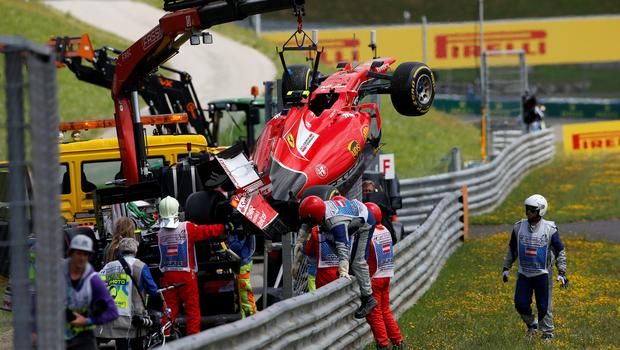Marshalls retrieve the car of Kimi Raikkonen after he crashed during the Formula One Grand Prix of Austria