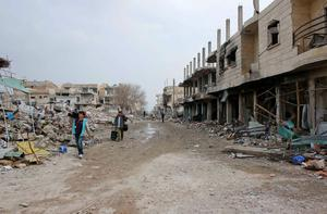 Members of a television crew walk along damaged buildings in the northern Syrian town of Kobani January 28, 2015. REUTERS/Osman Orsal